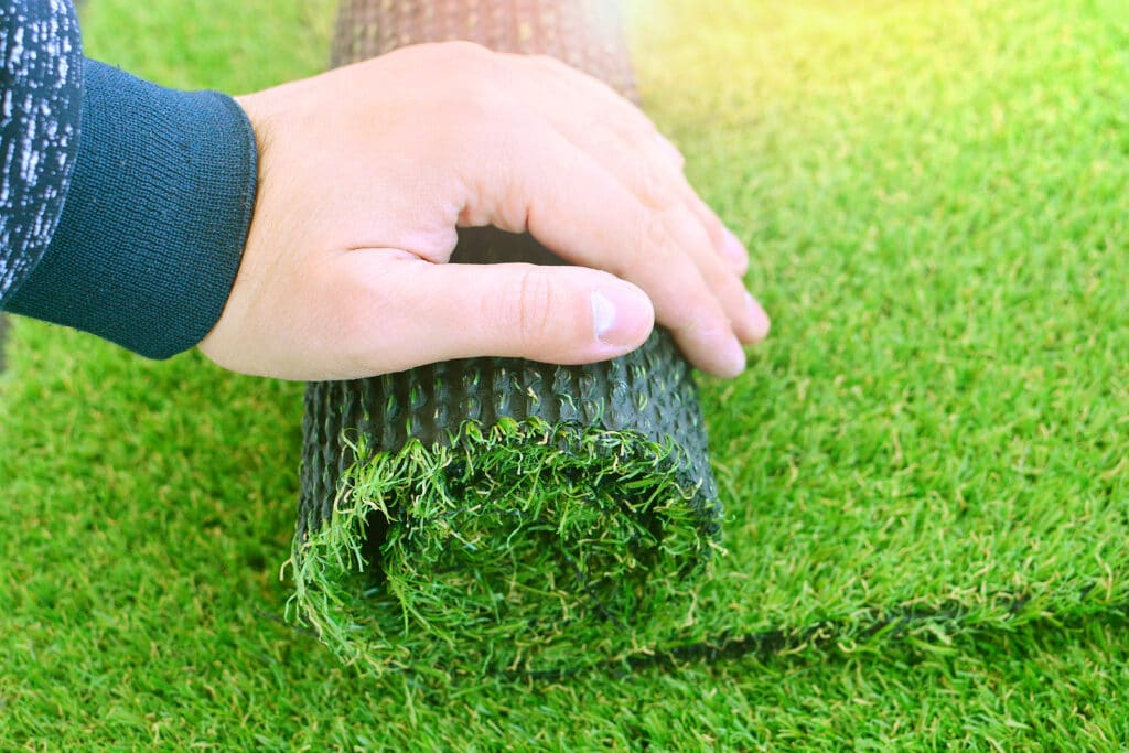 A worker rolling out a strip of artificial grass
