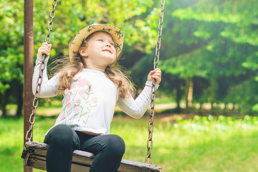 Girl enjoying a swing on grass