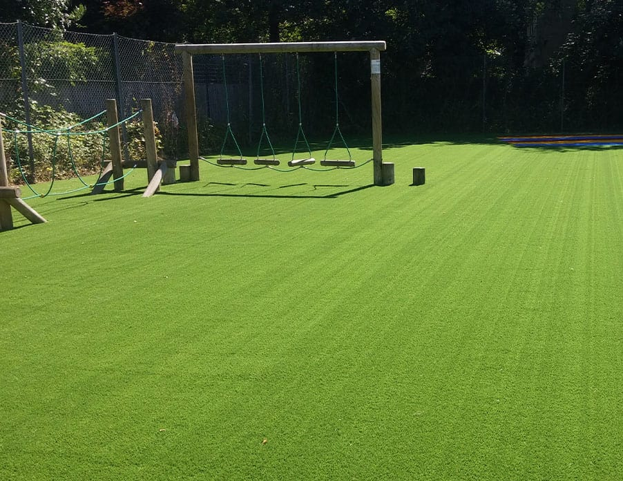 Artificial grass lawn with children's swings