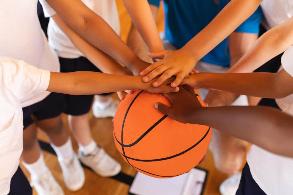 school children forming a hand stack on a basketball