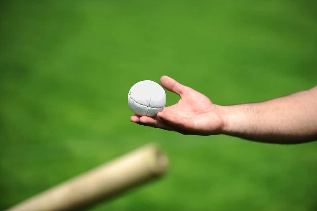 a hand holding a rounders ball at a school training session