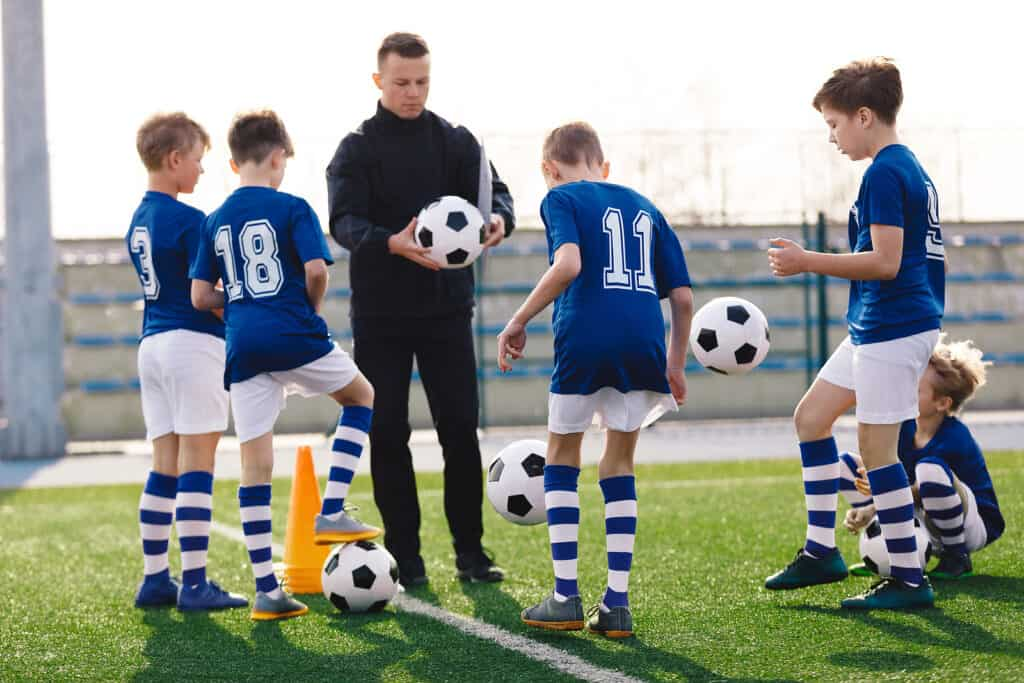 a coach teaching kids how to play football in school pe