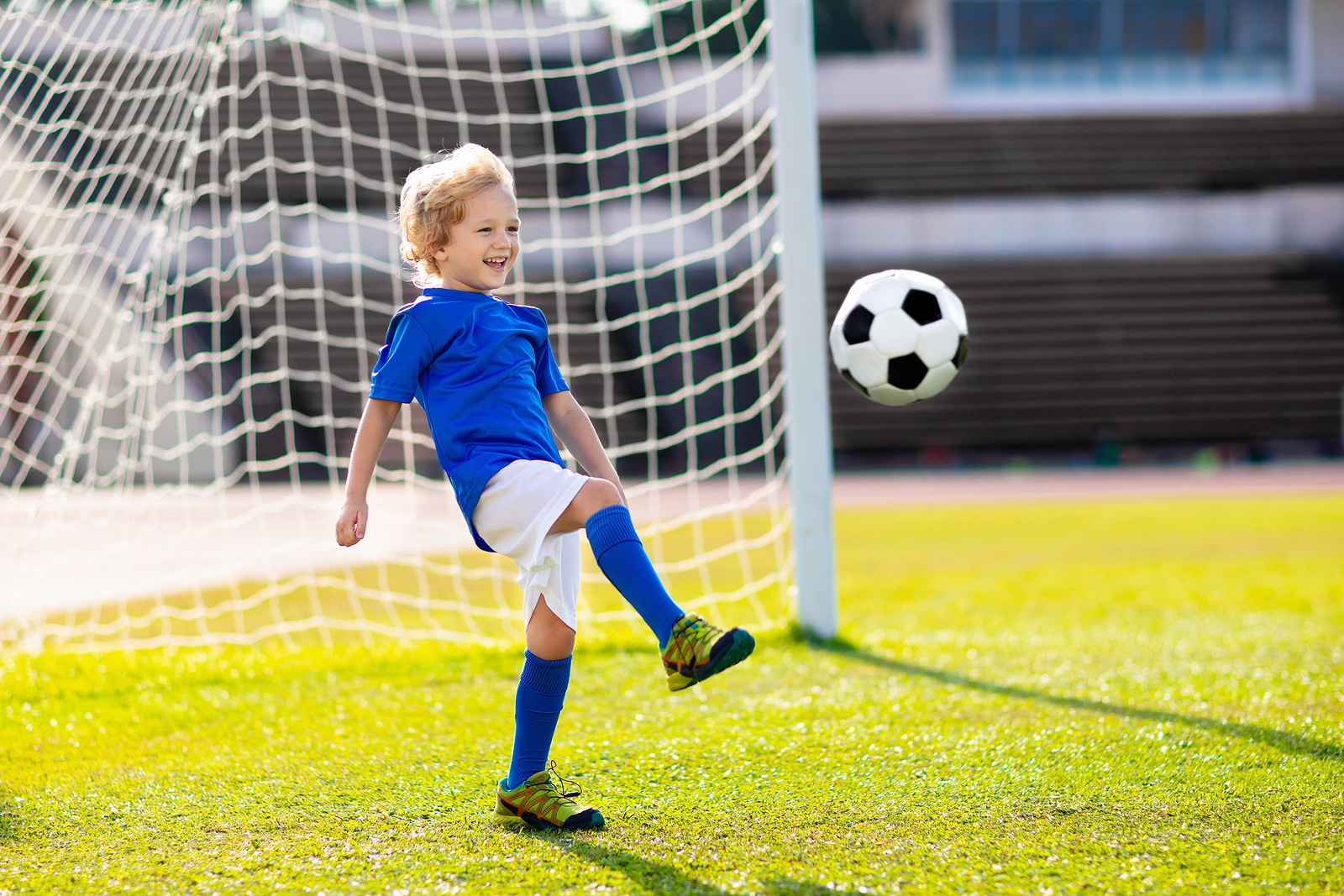 a kid in a football goal defending an oncoming shot at goal