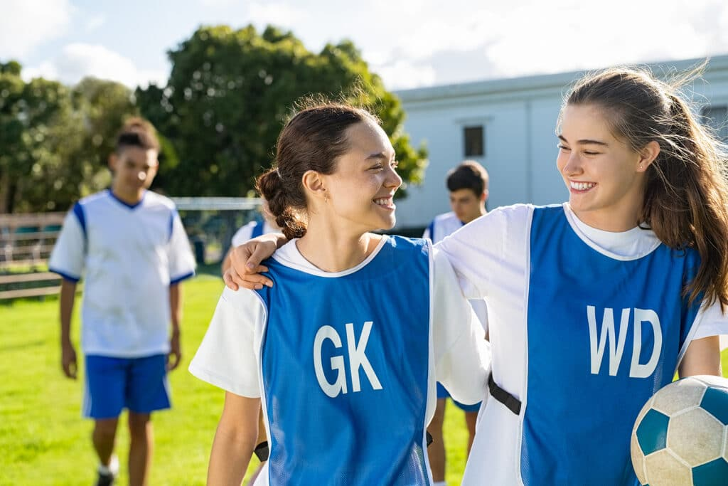 two girls in football training kit talking to each other after a school training session
